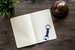 Buchhotel Halten Sie Glocke und Notizbuch an der Aufnahme auf dunklem Draufsichtmodell des Holztischs instand lizenzfreie stockbilder