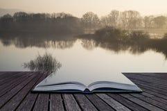 Buchkonzept Landschaft von See im Nebel mit Sonnenglühen bei Sonnenaufgang Stockfotos
