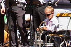Buchlovice, República Checa, o 29 de julho de 2017: O rapaz pequeno joga a trombeta em festividades populares Criança dotado Colh Foto de Stock