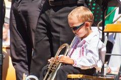 Buchlovice, República Checa, o 29 de julho de 2017: O rapaz pequeno joga a trombeta em festividades populares Criança dotado Colh Imagem de Stock Royalty Free