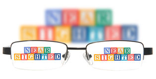 Buchstabe blockiert die Rechtschreibung, die mit einem Paar Gläsern kurzsichtig ist. Stockfoto