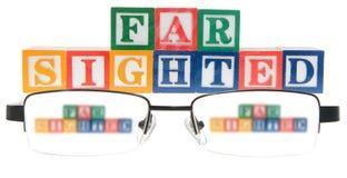 Buchstabe blockiert die Rechtschreibung, die weit mit einem Paar Gläsern anvisiert wird Stockbild
