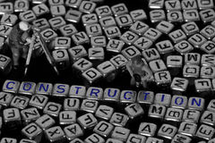 Buchstabe blockiert Rechtschreibungsbau mit vorbildlichen Bauarbeitern Stockfoto