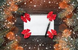 Buchstabe für Santa Claus auf schwarzem Hintergrund, Tannenbaumaste Raum für Text, Draufsicht Effekt von hellen Dokumentenmarken  lizenzfreies stockbild