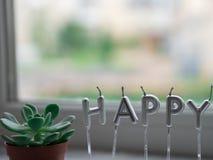 Buchstabe GLÜCKLICH von den Kerzen auf Fensterbretthintergrund Glückliches Konzept Stockbild