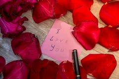 Buchstabe mit ich liebe dich Anmerkung, Rotrose und Stift Lizenzfreies Stockfoto
