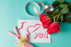 Buchstabe mit Liebesanmerkung, Rotrose mit Herzen Stockfoto