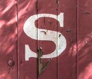 Buchstabe S auf Rot-gemaltem hölzernem Abstellgleise lizenzfreie stockfotos