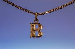 Buchstabeanhänger des Gold B, der an der goldenen Halskettenkette auf blauem Hintergrund hängt Stockfoto