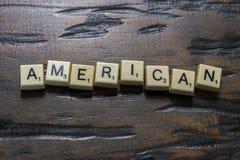 Buchstabefliese Amerika auf Woodgrain stockbild
