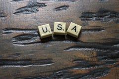 Buchstabefliese USA auf Woodgrain stockfotos