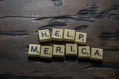 Buchstabefliesen-Hilfen-merica auf Woodgrain lizenzfreie stockbilder