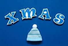 Buchstaben des blauen Papiers und Spielzeughut auf dem blauen ackground Stockbilder