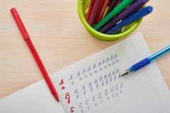 Buchstaben in einem Notizbuch zeichnen an Lizenzfreie Stockbilder