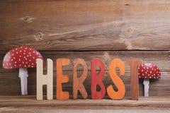 Herbst hintergrund. Buchstaben ergeben das wort herbst vor holzhintergrund royalty free stock photo