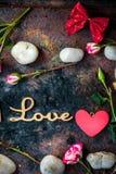 Buchstaben LIEBEN auf rustikalem Hintergrund mit Herzen und Blumen Lizenzfreies Stockbild