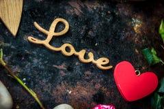 Buchstaben LIEBEN auf rustikalem Hintergrund mit Herzen und Blumen Lizenzfreie Stockbilder