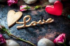Buchstaben LIEBEN auf rustikalem Hintergrund mit Herzen und Blumen Lizenzfreies Stockfoto