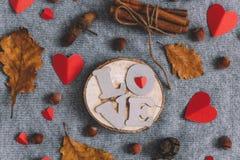 Buchstaben LIEBEN Herzzimtstangebündelnüsse und -Herbstlaub stockbilder