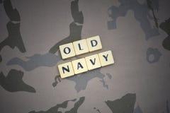 Buchstaben mit alter Marine des Textes auf dem kakifarbigen Hintergrund Grüne taktische Schutzkleidung mit US-Streifenmarkierungs Stockbild