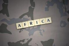 Buchstaben mit Text Afrika auf dem kakifarbigen Hintergrund Grüne taktische Schutzkleidung mit US-Streifenmarkierungsfahne und Na Lizenzfreies Stockbild