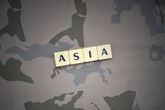 Buchstaben mit Text Asien auf dem kakifarbigen Hintergrund Grüne taktische Schutzkleidung mit US-Streifenmarkierungsfahne und Nah Lizenzfreies Stockfoto