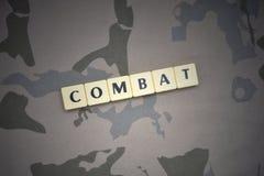 Buchstaben mit Text bekämpfen auf dem kakifarbigen Hintergrund Grüne taktische Schutzkleidung mit US-Streifenmarkierungsfahne und Stockfotografie