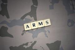 Buchstaben mit Text bewaffnet auf dem kakifarbigen Hintergrund Grüne taktische Schutzkleidung mit US-Streifenmarkierungsfahne und Stockbild