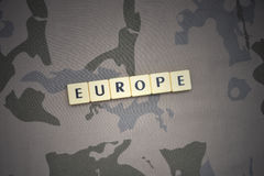 Buchstaben mit Text Europa auf dem kakifarbigen Hintergrund Grüne taktische Schutzkleidung mit US-Streifenmarkierungsfahne und Na Lizenzfreie Stockfotos
