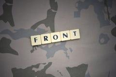 Buchstaben mit Text konfrontieren auf dem kakifarbigen Hintergrund Grüne taktische Schutzkleidung mit US-Streifenmarkierungsfahne Lizenzfreies Stockbild