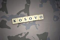 Buchstaben mit Text Kosovo auf dem kakifarbigen Hintergrund Grüne taktische Schutzkleidung mit US-Streifenmarkierungsfahne und Na Stockfoto