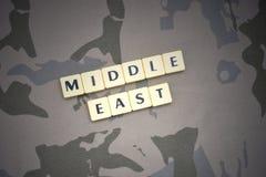 Buchstaben mit Text Mittlerer Osten auf dem kakifarbigen Hintergrund Grüne taktische Schutzkleidung mit US-Streifenmarkierungsfah Lizenzfreie Stockfotos