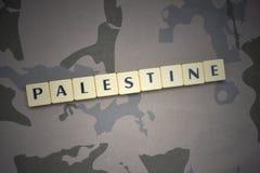 Buchstaben mit Text Palästina auf dem kakifarbigen Hintergrund Grüne taktische Schutzkleidung mit US-Streifenmarkierungsfahne und Lizenzfreies Stockbild