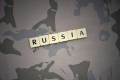 Buchstaben mit Text Russland auf dem kakifarbigen Hintergrund Grüne taktische Schutzkleidung mit US-Streifenmarkierungsfahne und  Stockfotos