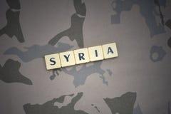 Buchstaben mit Text Syrien auf dem kakifarbigen Hintergrund Grüne taktische Schutzkleidung mit US-Streifenmarkierungsfahne und Na Lizenzfreies Stockbild