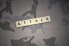 Buchstaben mit Textangriff auf dem kakifarbigen Hintergrund Grüne taktische Schutzkleidung mit US-Streifenmarkierungsfahne und Na Lizenzfreie Stockfotografie