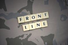 Buchstaben mit Textfrontlinie auf dem kakifarbigen Hintergrund Grüne taktische Schutzkleidung mit US-Streifenmarkierungsfahne und Stockfoto