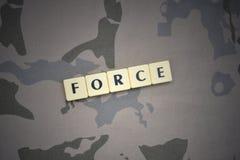 Buchstaben mit Textkraft auf dem kakifarbigen Hintergrund Grüne taktische Schutzkleidung mit US-Streifenmarkierungsfahne und Naha Lizenzfreies Stockfoto