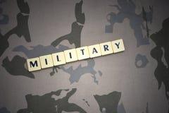 Buchstaben mit Textmilitär auf dem kakifarbigen Hintergrund Konzept Lizenzfreies Stockbild