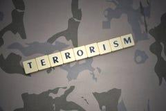 Buchstaben mit Textterrorismus auf dem kakifarbigen Hintergrund Grüne taktische Schutzkleidung mit US-Streifenmarkierungsfahne un Lizenzfreies Stockfoto