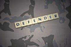 Buchstaben mit Textverteidiger auf dem kakifarbigen Hintergrund Grüne taktische Schutzkleidung mit US-Streifenmarkierungsfahne un Stockfoto