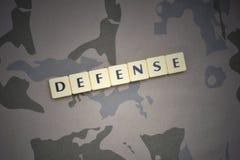 Buchstaben mit Textverteidigung auf dem kakifarbigen Hintergrund Grüne taktische Schutzkleidung mit US-Streifenmarkierungsfahne u Stockbilder