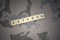 Buchstaben mit Textveteran auf dem kakifarbigen Hintergrund Grüne taktische Schutzkleidung mit US-Streifenmarkierungsfahne und Na Stockfoto