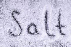 Buchstaben salzen auf den Salzkristallen auf einem schwarzen Hintergrund Lassen Sie Stockfotografie