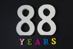 Buchstaben und Zahlen achtundachzig Jahre alt auf einem schwarzen Hintergrund Stockfotografie