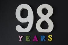 Buchstaben und Zahlen achtundneunzig Jahre alt auf einem schwarzen Hintergrund Stockbild