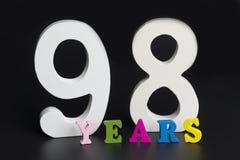 Buchstaben und Zahlen achtundneunzig Jahre alt auf einem schwarzen Hintergrund Lizenzfreies Stockbild