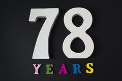 Buchstaben und Zahlen achtundsiebzig Jahre alt auf einem schwarzen Hintergrund Stockbild