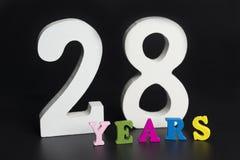 Buchstaben und Zahlen achtundzwanzig Jahre auf einem schwarzen Hintergrund Stockbilder