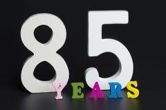 Buchstaben und Zahlen-achtzig-fünf auf dem schwarzen Hintergrund Lizenzfreie Stockfotografie